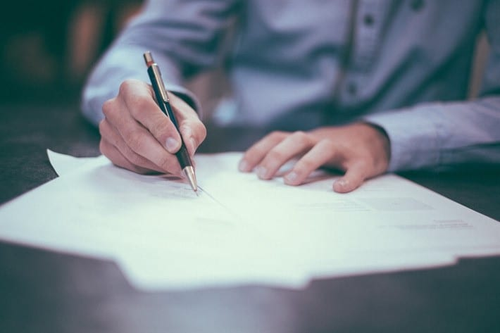 man signing title loan agreement